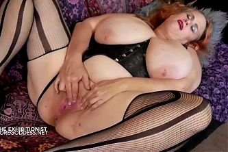 Redhead with huge tits exhibits herself